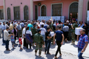Displaced Christians wait for humanitarian aid at a church in Hamdaniya town